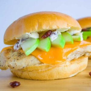 Two granny smith chicken sandwiches sitting on wood cutting board