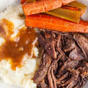 White plate of pot roast, carrots, celery, mashed potatoes and gravy