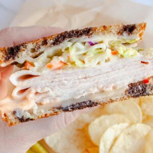 Hand holding a half of Rachel Sandwich