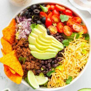 White bowl of Taco Salad next to avocado, limes and dressing
