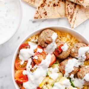 Greek Turkey Meatballs in a white bowl with orzo, cucumber, tomato & tzatziki sauce