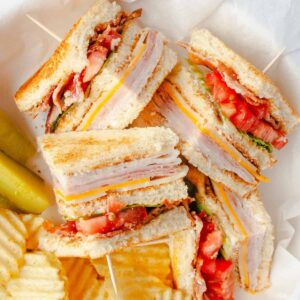 Quartered clubhouse sandwich with potato chips and pickles