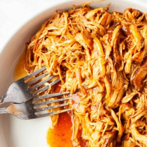 Slow Cooker BBQ Ranch Chicken in a white dish with two forks